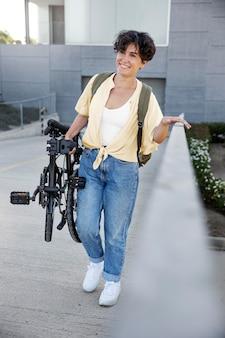 Jonge vrouw die haar vouwfiets gebruikt