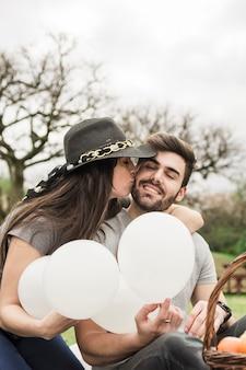 Jonge vrouw die haar vriend kussen die witte ballons in hand houden