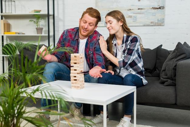 Jonge vrouw die haar vriend tevredenstellen na het verwijderen van het houten blok van toren thuis