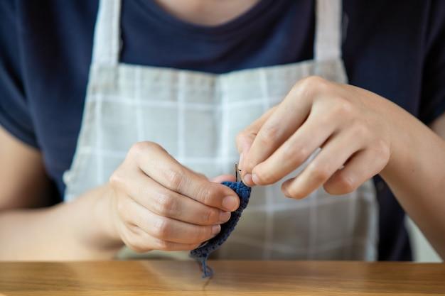 Jonge vrouw die haar vrije tijd doorbrengt met de handwerkhobby. bekwame vrouw die een gehaakte hoed en tas maakt tijdens verblijf thuis. het inspiratie- en creativiteitsconcept met kopie ruimte.