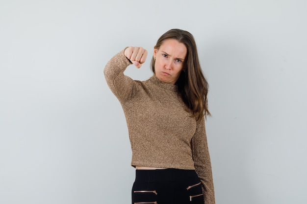 Jonge vrouw die haar vuist in gouden blouse toont en strikt kijkt
