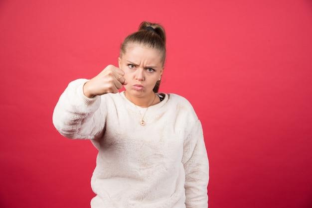 Jonge vrouw die haar vuist op een rode muur toont