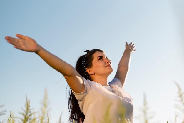 Jonge vrouw die haar wapens in de lucht houdt en de hemel bekijkt