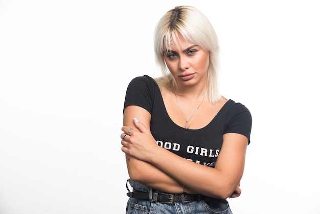 Jonge vrouw die haar wapens op witte muur kruist.