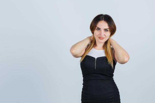 Jonge vrouw die haarlokken vasthoudt en er aantrekkelijk uitziet