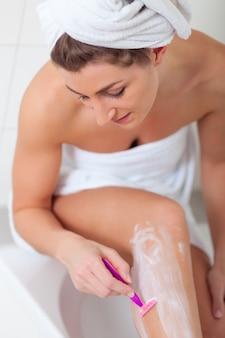 Jonge vrouw die haarverwijdering doet bij benen