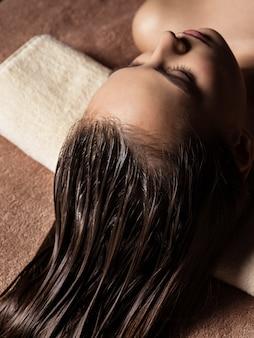 Jonge vrouw die haarzorgprocedure in kuuroordsalon ontvangt. schoonheidsbehandeling. spa salon