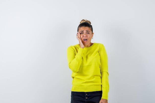 Jonge vrouw die hand bij mond houdt, mond wijd open houdt in gele trui en zwarte broek en verbaasd kijkt looking
