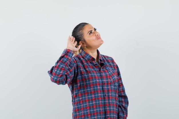 Jonge vrouw die hand dichtbij oor zet zoals het proberen om in gecontroleerd overhemd te horen en ernstig, vooraanzicht kijkt.