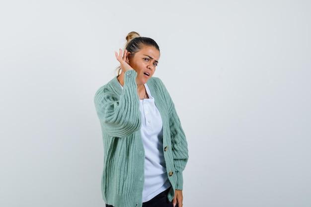 Jonge vrouw die hand in de buurt van oor houdt om iets te horen in wit t-shirt en mintgroen vest en er gefocust uitziet