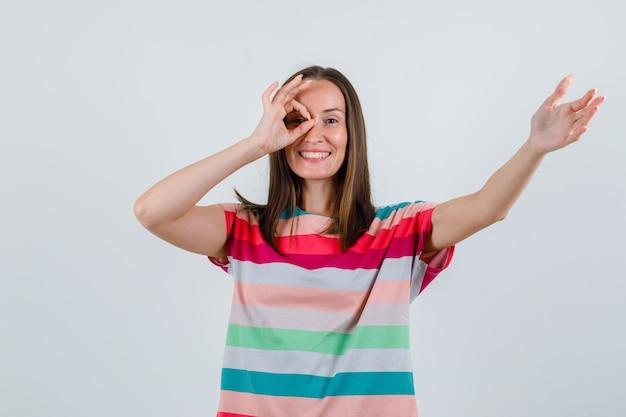 Jonge vrouw die hand met ok teken op oog in t-shirt uitrekt en vrolijk kijkt. vooraanzicht.