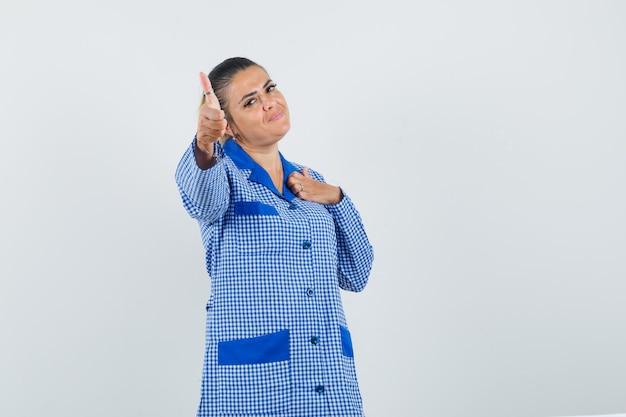 Jonge vrouw die hand op borst in blauw geruit pyjamaoverhemd richt en vasthoudt en er mooi uitziet, vooraanzicht.