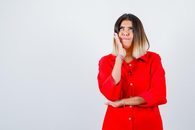 Jonge vrouw die hand op de wang houdt in een rood oversized shirt en er attent uitziet, vooraanzicht.