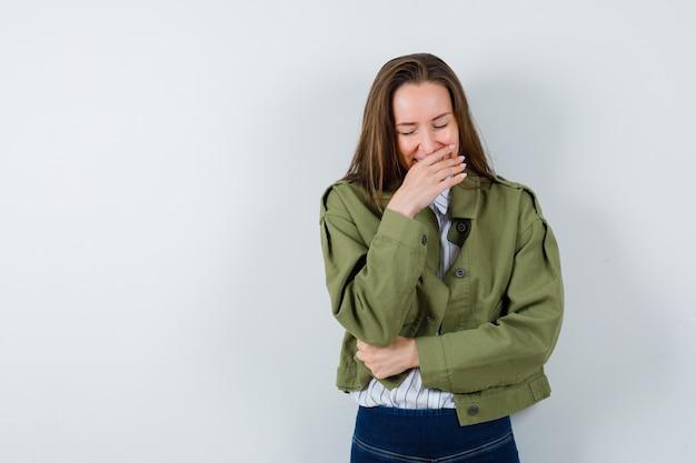 Jonge vrouw die hand op mond in overhemd, jasje houdt en vrolijk kijkt, vooraanzicht.