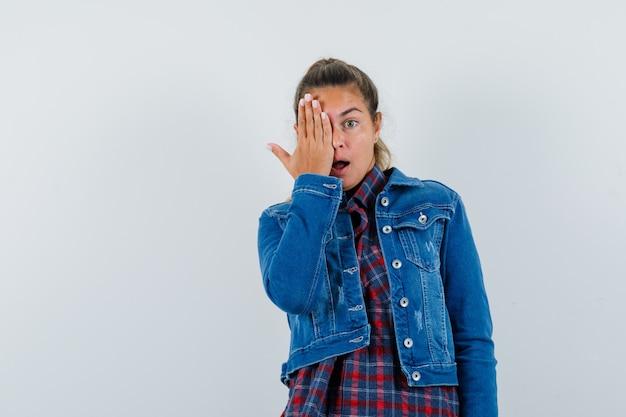 Jonge vrouw die hand op oog in overhemd, jasje houdt en verbaasd kijkt. vooraanzicht.