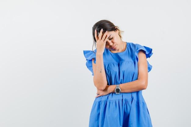 Jonge vrouw die hand op voorhoofd houdt in blauwe jurk en er uitgeput uitziet