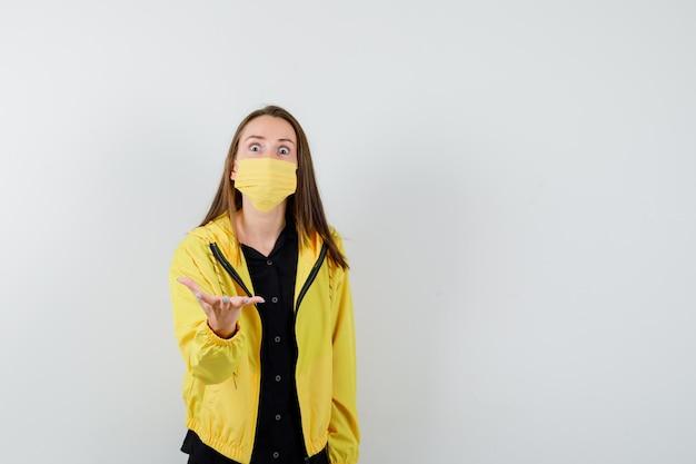 Jonge vrouw die hand op vragende manier uitrekt en verbaasd kijkt