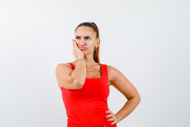 Jonge vrouw die hand op wang houdt terwijl hand op taille in rode tanktop wordt gehouden en doordacht, vooraanzicht kijkt.