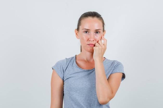 Jonge vrouw die hand op wang in grijs t-shirt houdt en teleurgesteld kijkt. vooraanzicht.