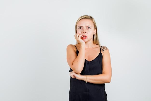 Jonge vrouw die hand op wang in zwart hemd houdt en bezorgd kijkt.