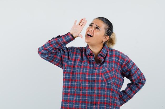 Jonge vrouw die hand opheft dichtbij mond, iemand in gecontroleerd overhemd roept en er mooi uitziet. vooraanzicht.