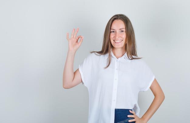 Jonge vrouw die hand opheft en in wit t-shirt glimlacht