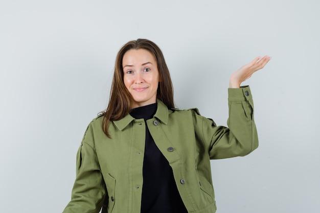 Jonge vrouw die hand opheft voor het tonen van iets in groen jasje en optimistisch kijkt. vooraanzicht.