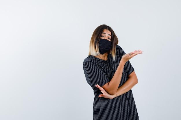 Jonge vrouw die hand uitrekt als iets vasthoudt, hand onder de elleboog houdt in zwarte jurk, zwart masker en er mooi uitziet. vooraanzicht.