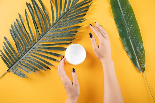 Jonge vrouw die handcrème aanbrengt aan tafel met bladeren op een oranje achtergrond Premium Foto