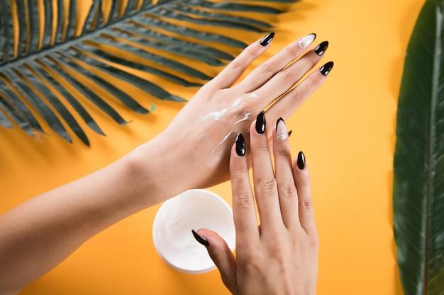 Jonge vrouw die handcrème aanbrengt aan tafel met bladeren op een oranje achtergrond