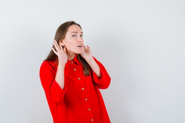 Jonge vrouw die handen achter de oren in rode blouse houdt en nieuwsgierig kijkt, vooraanzicht.