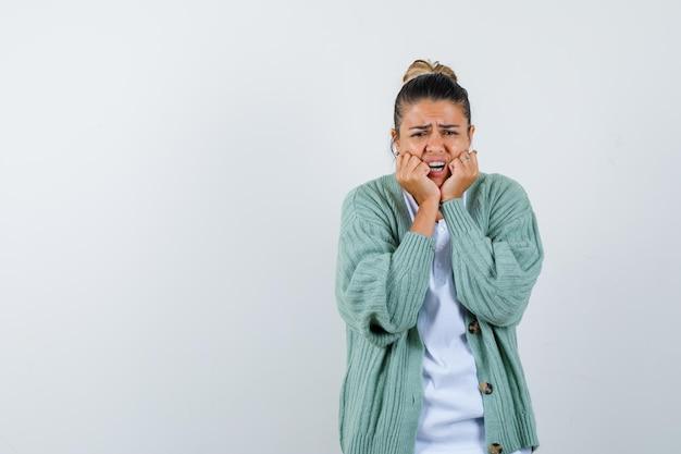 Jonge vrouw die handen in de buurt van mond zet in wit overhemd en mintgroen vest en er bang uitziet and
