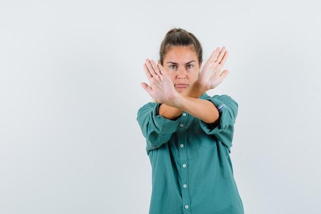 Jonge vrouw die handen kruist die x-teken of stopgebaar in groene blouse toont en er schattig uitziet