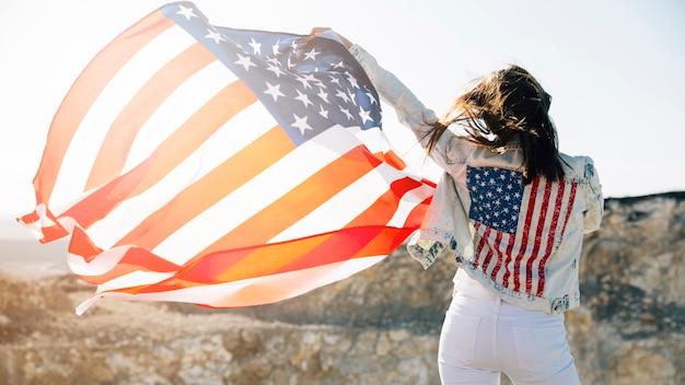 Jonge vrouw die handen met amerikaanse vlag opheft