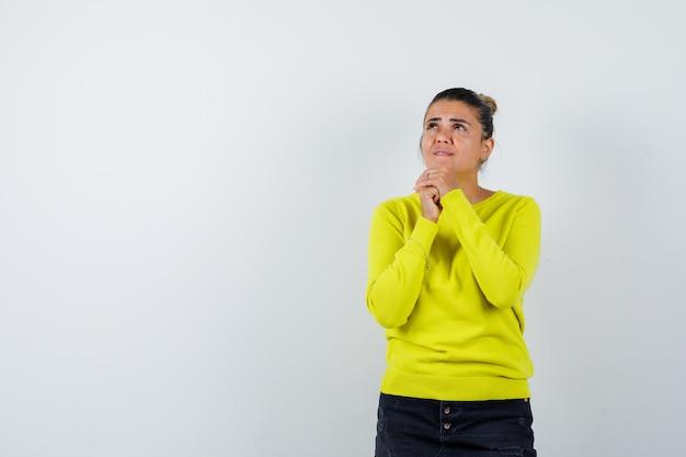 Jonge vrouw die handen omklemt, naar boven kijkt in gele trui en zwarte broek en peinzend kijkt