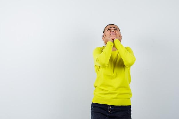 Jonge vrouw die handen op de wangen legt, naar boven kijkt in gele trui en zwarte broek en er gelukkig uitziet