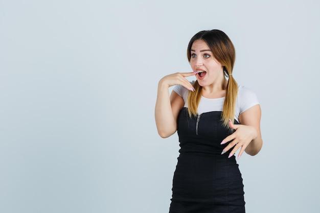 Jonge vrouw die handen op een verbaasde manier uitrekt