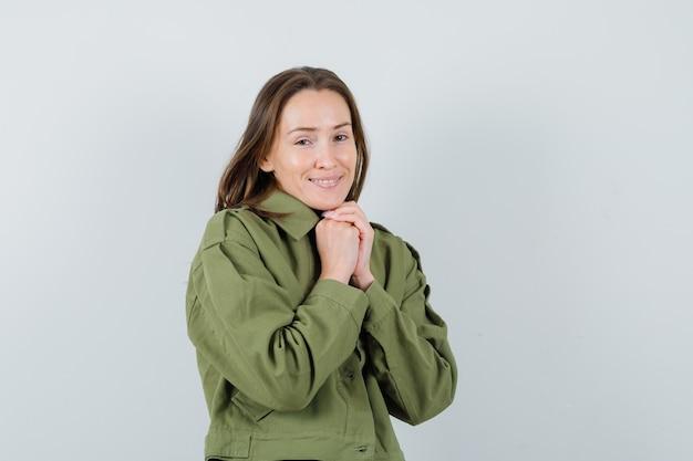 Jonge vrouw die handen op haar borst in groen jasje combineert en tevreden kijkt. vooraanzicht.
