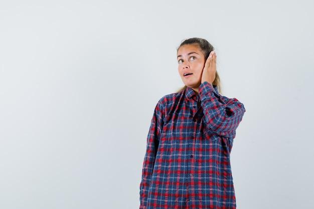 Jonge vrouw die handen op oor in gecontroleerd overhemd drukt en mooi kijkt
