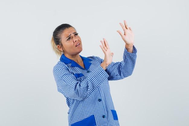Jonge vrouw die handen opheft als iets in het blauwe overhemd van de gingangpyjama en ziet er moe tegen te houden. vooraanzicht.