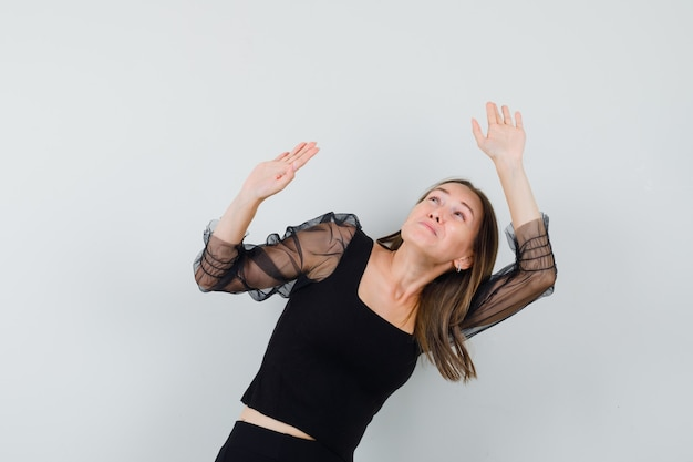 Jonge vrouw die handen opheft als iets zwaars in zwarte blouse en zwarte broek vast te houden en er moe uit te zien. vooraanzicht.