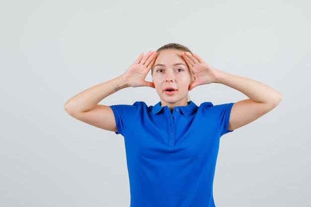 Jonge vrouw die handen opheft om duidelijk in blauw t-shirt te zien en nieuwsgierig kijkt