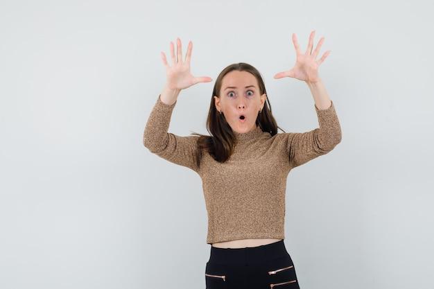 Jonge vrouw die handen opheft om iemand in goud gleden trui en zwarte broek te bedreigen en verbaasd te kijken. vooraanzicht.