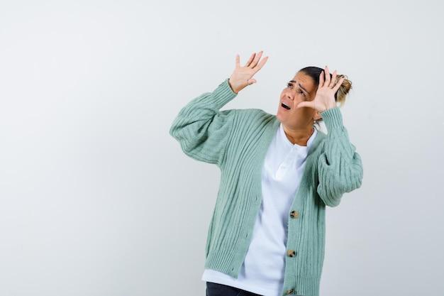 Jonge vrouw die handen opsteekt en naar boven kijkt in wit t-shirt en mintgroen vest en er bang uitziet