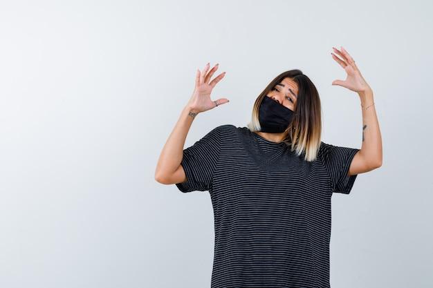 Jonge vrouw die handen uitrekt als iets in zwarte jurk, zwart masker vasthoudt en bang kijkt. vooraanzicht.