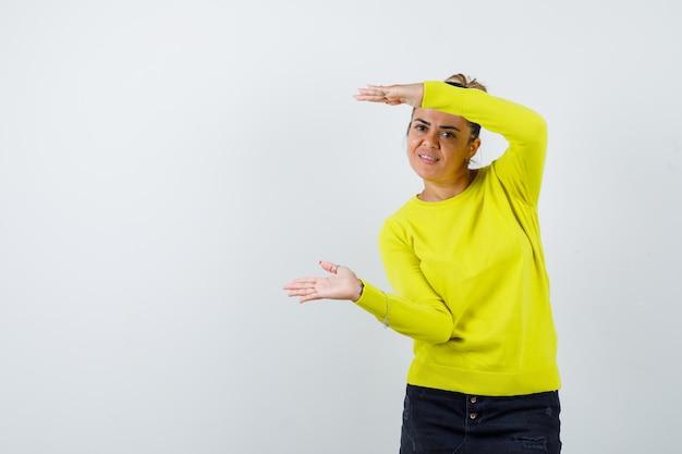 Jonge vrouw die handen uitrekt alsof ze iets vasthoudt, schubben toont in gele trui en zwarte broek en er gelukkig uitziet