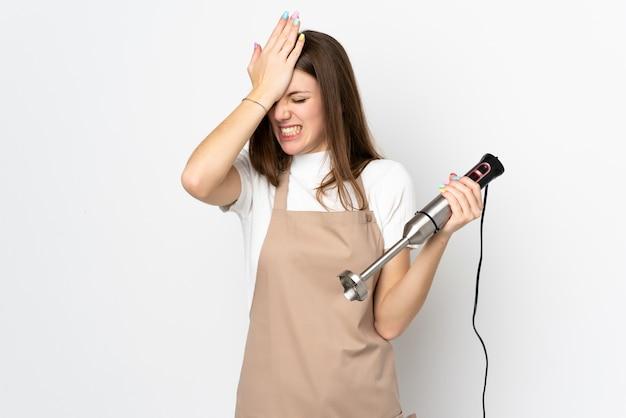 Jonge vrouw die handmixer op witte muur gebruiken die twijfels met verwarde gezichtsuitdrukking hebben