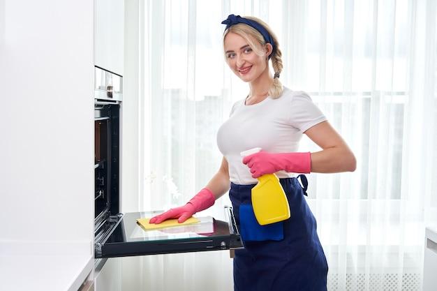 Jonge vrouw die handschoenen draagt die oven in de keuken schoonmaken. schoonmaak dienstverleningsconcept