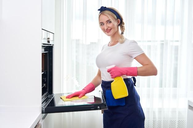 Jonge vrouw die handschoenen draagt die oven in de keuken schoonmaken.