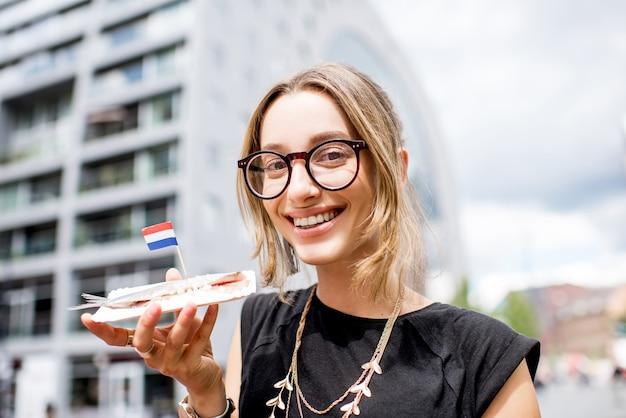 Jonge vrouw die haring eet met uien traditionele nederlandse snack in de buurt van de rotterdamse markt